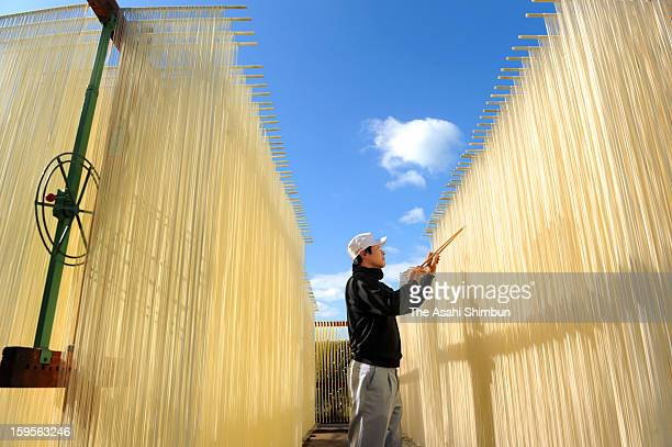 A worker hungs rows of Japanese somen to dry in the winter sun on January 10 2013 in Tonosho Kagawa Japan The thin wheat noodles forming white...