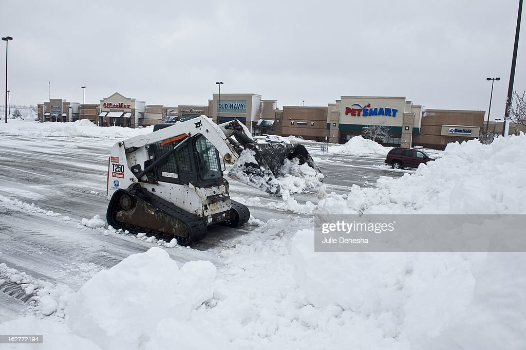 A worker in a Bobcat works to clear snow from a parking lot after a snowstorm hit the midwest February 26, 2013 in Merriam, Kansas. This is the second major snowstorm the midwest has seen this week dropping a half-foot or more of snow across Missouri and Kansas and cutting power to thousands.