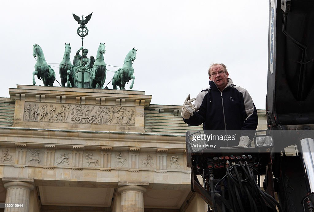 A worker in a cherry picker truck directs co-workers as they erect a large nine-armed candleholder, a Hannoukiah, or Menorah, ahead of the start of the eight-day-long and annual Jewish Festival of Lights known as Chanukah, in front of the Brandenburg Gate on December 20, 2011 in Berlin, Germany. The festival marks the rebellion of Maccabee Jews against the Greeks in 165 BC, which some believers say included a number of miracles pointing to divine providence.