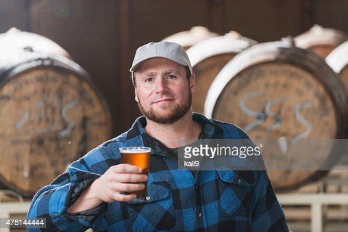 Worker in a microbrewery holding glass of beer