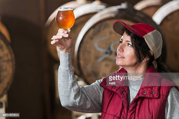 Worker in a microbrewery inspecting glass of beer