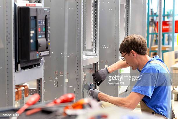 Worker in a switchboard construction factory