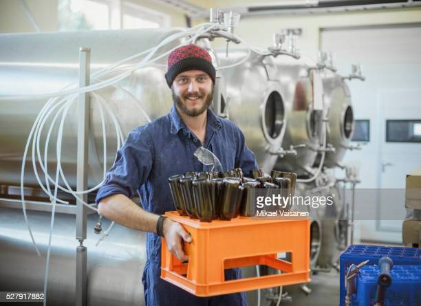 worker in blue overall in microbrewery