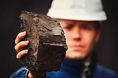 Worker is showing lignite - often referred to as brown coal