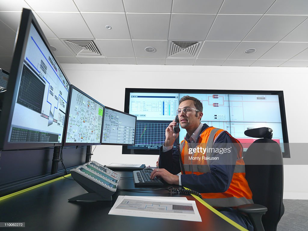 Worker in control room with screens
