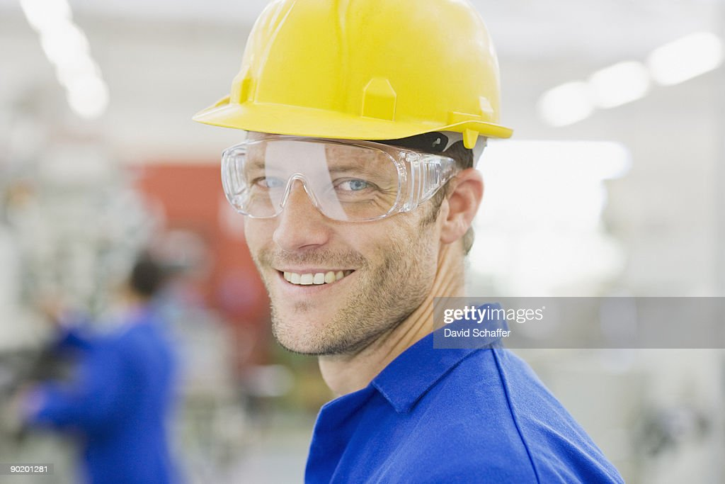 Worker in coveralls and safety goggles smiling : Stock Photo