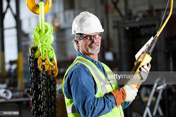 Worker in factory with industrial hook and chains