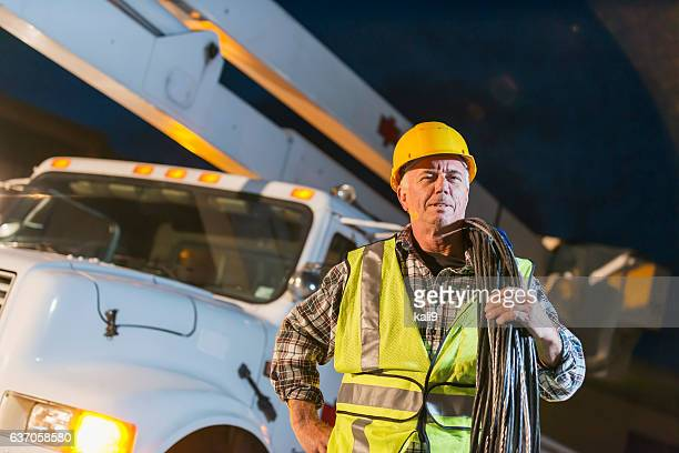 Worker in hardhat and safety vest outside truck