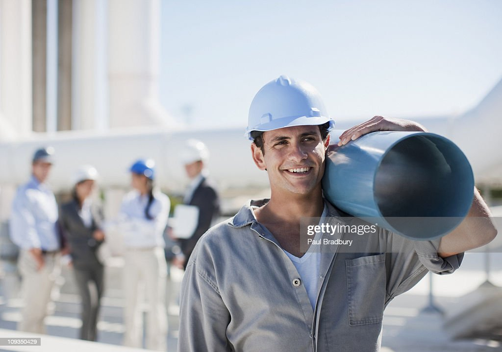 Worker in hard-hat carrying large pipe outdoors : Stock Photo