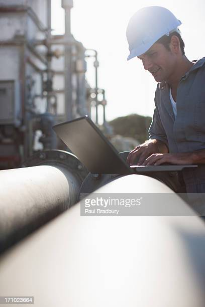 Worker in hard-hat using laptop