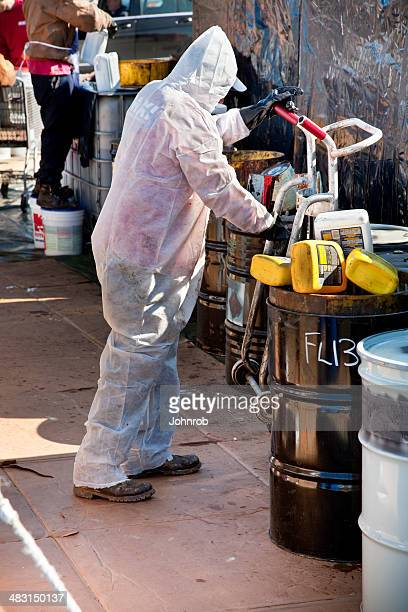 Worker in hazmat suit moving drum at Hazardous Waste collection