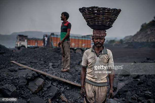 A worker in Jharia is loading a truck with coal using baskets that he carries on top of his head Jharia in India's eastern Jharkand state is...