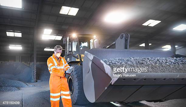 Worker in mineral store inspecting handful of metal alloy next to digger