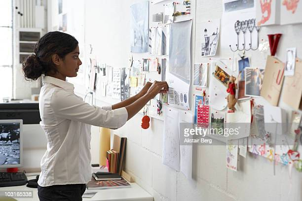 Worker in office pinning picture on wall