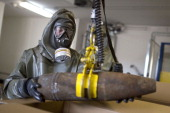 Worker in protective clothing unloads a dummy grenade during a press day at the GEKA facility on March 5 2014 in Munster Germany GEKA is...