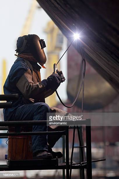 Worker in protective gear welding new plates on ship's hull.