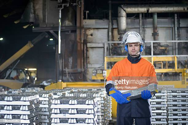Worker in protective workwear carrying aluminium ingot in foundry