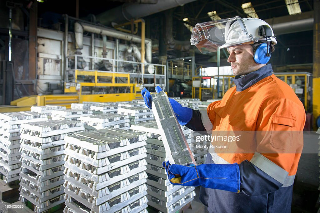 Worker in protective workwear inspecting aluminium ingot in foundry : Stock Photo