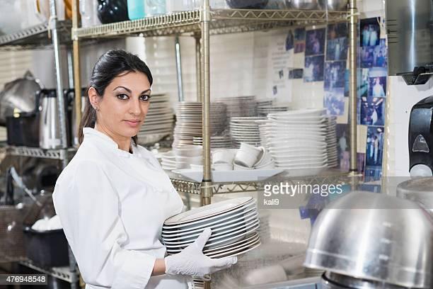 Arbeiter im restaurant tragen Stapel von Platten