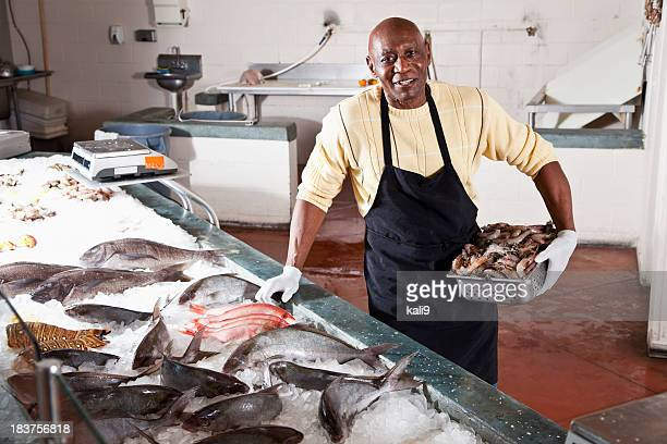 Worker in seafood market by fresh fish display