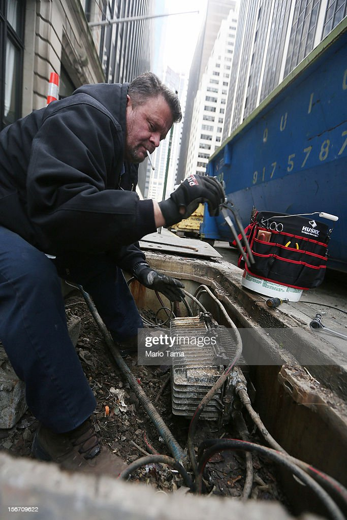 A worker in the Financial District inspects a flood damaged fiber optic node as they restore broadband services following Superstorm Sandy in lower Manhattan on November 19, 2012 in New York City. Many of the office towers in the low lying Financial District which flooded remain closed due to damage to heating and electrical infrastructure. Many other buildings in the area are being powered by generators.