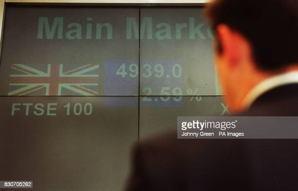 A worker in the London Stock Exchange in the City of London looking at a board showing the FTSE 100 Index plunging below the 5000 mark for the first...