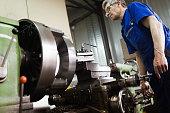 Industrial metal worker working on metal components in metal factory
