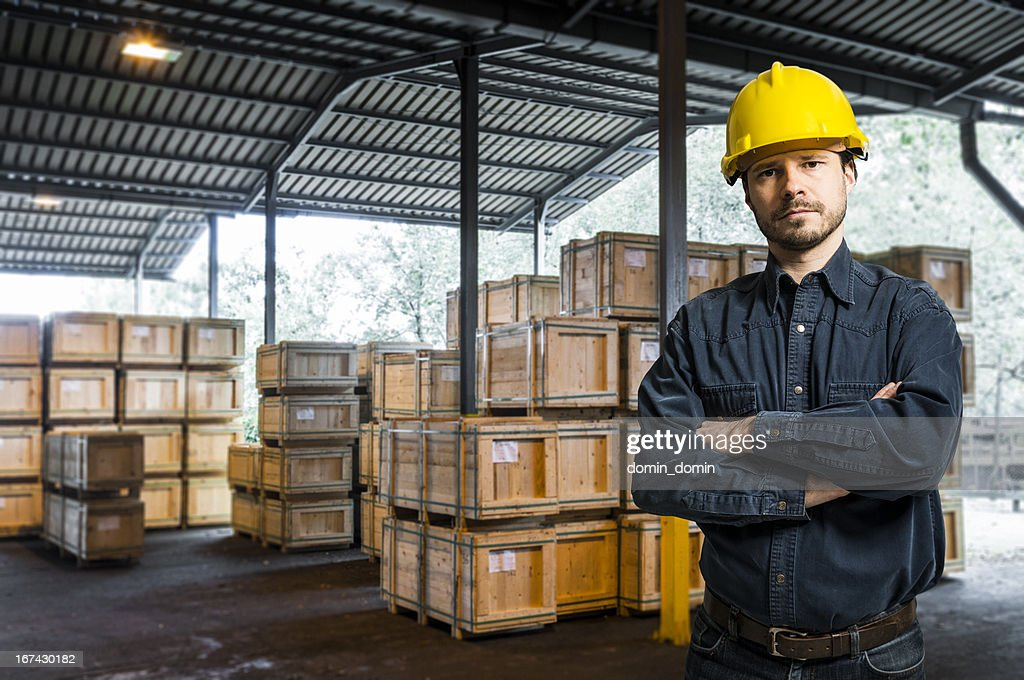 Worker in yellow helmet standing against warehouse with boxes, packages : Stock Photo