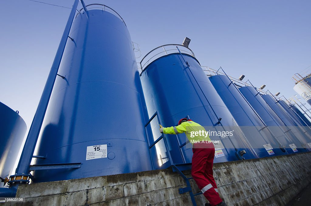 Worker inpsecting chemical storage tanks