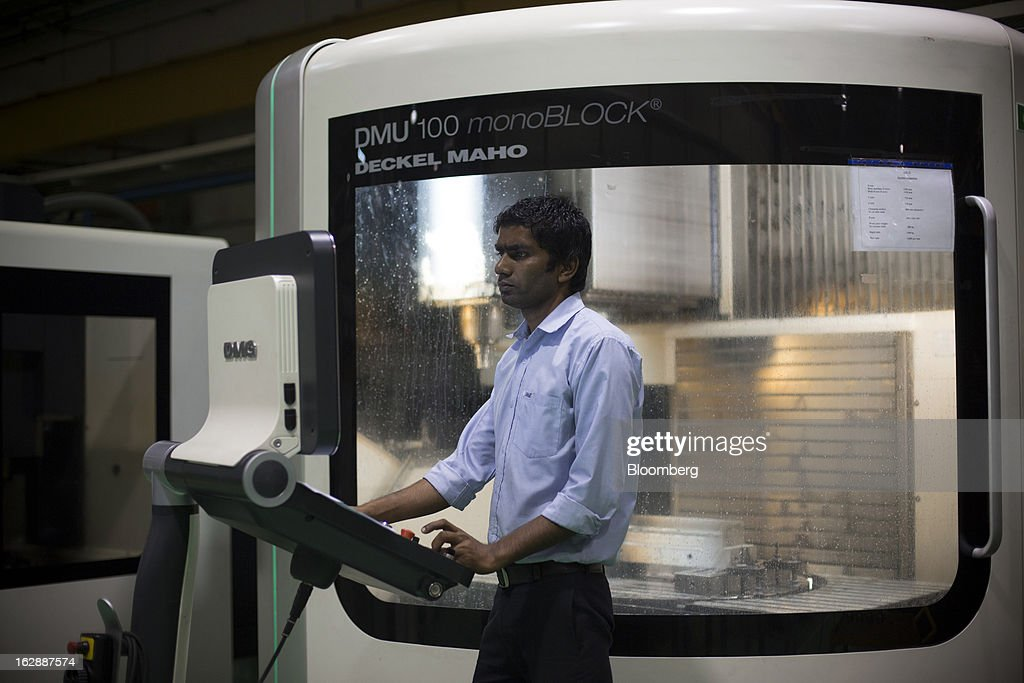 A worker inputs data into a DMG Mori Seiki GmbH DMU 100 monoBLOCK universal milling machine at the Motherson Sumi Systems Ltd. (MSSL) injection molding plant in Noida, India, on Thursday, Feb. 28, 2013. Motherson Sumi Systems Ltd., 25 percent owned by Sumitomo Electric Industries Ltd. and India's biggest auto parts maker, supplies rear view mirrors, bumpers and body panels to clients including Porsche Automobil Holding SE, Bayerische Motoren Werke AG and Volkswagen AG. Photographer: Brent Lewin/Bloomberg via Getty Images