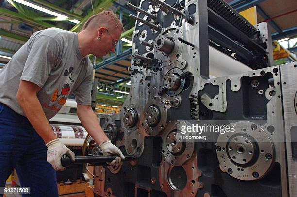 A worker inserts a rod into a printing press during its assembly at the manufacturing headquarters of Heidelberger Druckmaschinen near Heidelberg...