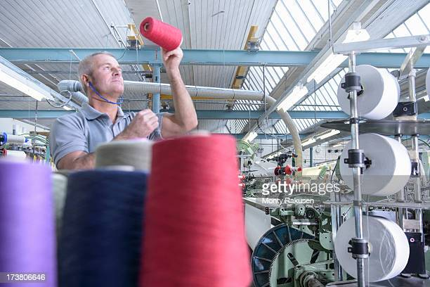 Worker inspecting bobbins of coloured thread in textile mill