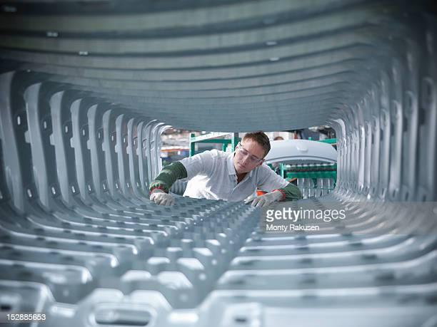 Worker inspecting car body pressings in car factory