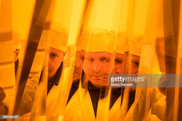 Worker inspecting circuit board under photographically safe light in circuit board factory, close up