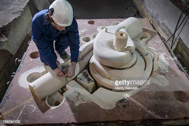 Worker inspecting complex mould before pouring molten metal in foundry