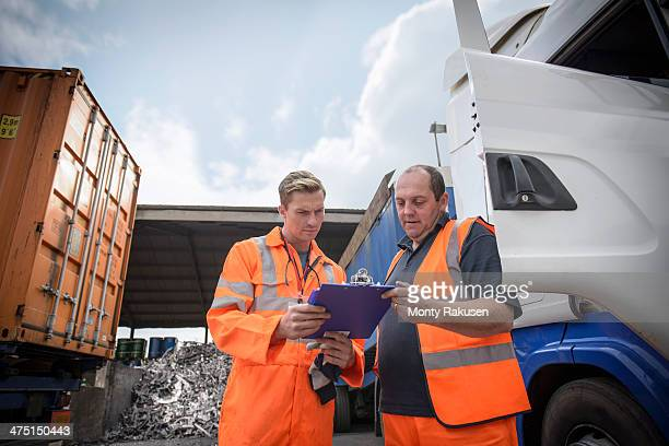 Worker inspecting delivery paperwork with truck driver