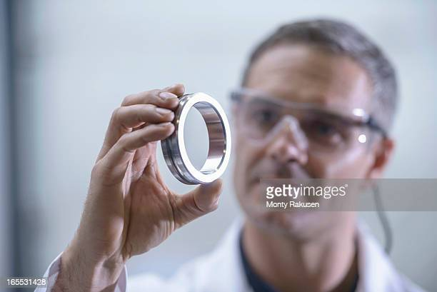 Worker inspecting engineering parts that have been cleaned using ultrasonics
