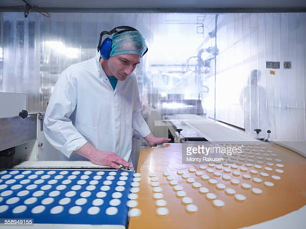 Worker inspecting fondant mint in chocolate factory