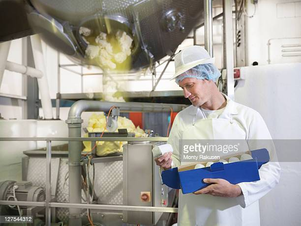 Worker inspecting goats butter in dairy