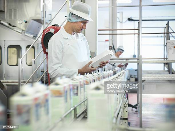 Worker inspecting goat's milk in dairy