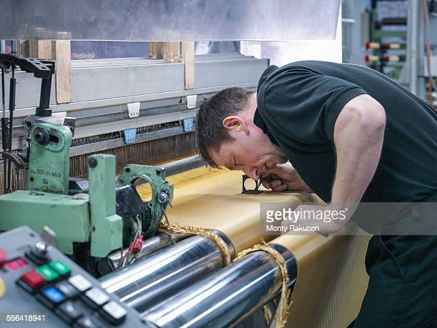 Worker inspecting kevlar fabric in carbon fibre factory