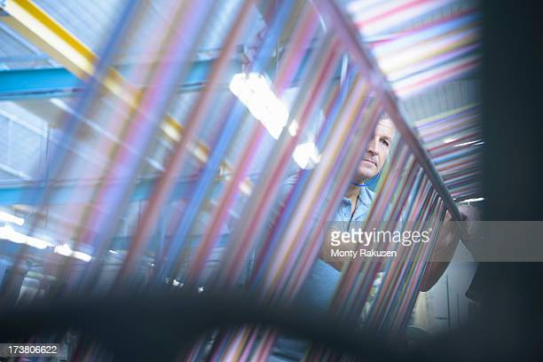 Worker inspecting multicoloured threads on industrial loom in textile mill
