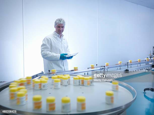 Worker inspecting packaging in pharmaceutical factory