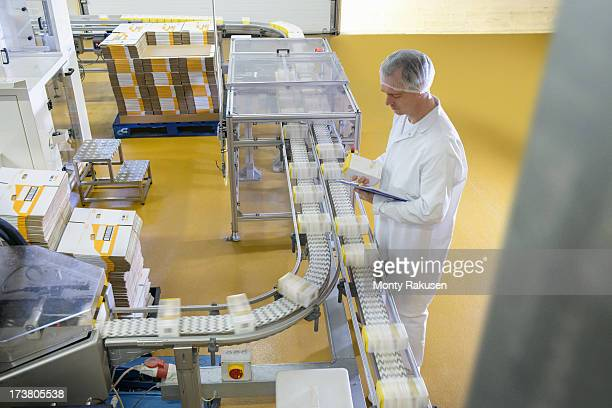 Worker inspecting packed products on conveyor belt in biscuit factory
