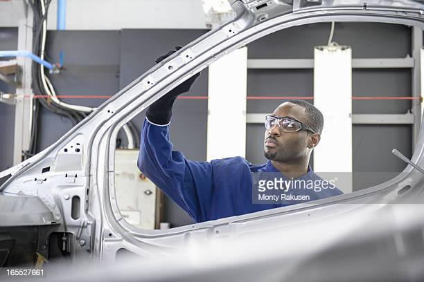 Worker inspecting paint finish in car factory