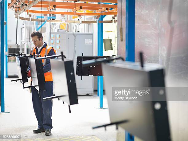 Worker inspecting painted parts in sheet metal factory