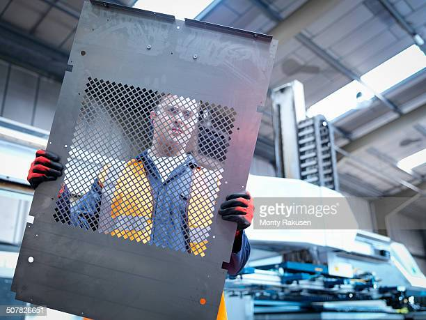 Worker inspecting parts next to robotic metal cutting machine in sheet metal factory