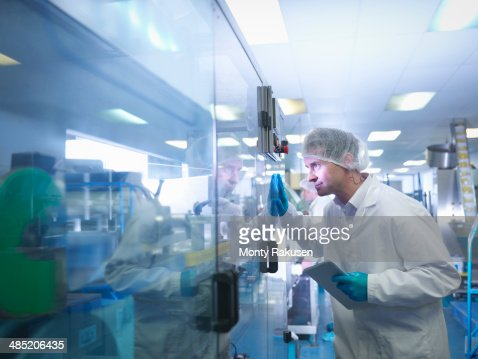 Worker inspecting tablets as they are put into packaging in pharmaceutical factory