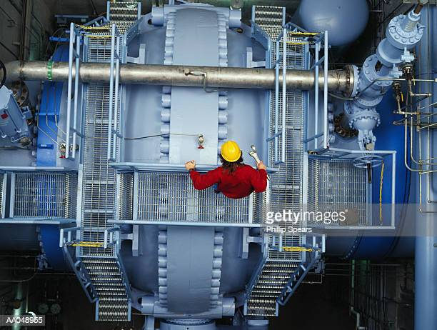 Worker inspecting valve at power station. overhead view