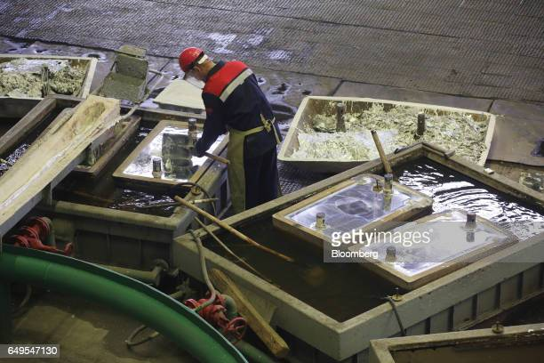 A worker inspects a cooling zinc ingot in the rotary foundry room at the Chelyabinsk Zinc Plant operated by Ural Mining and Metallurgical Co in...